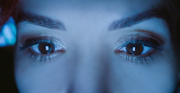 Woman looking at a screen with blue light reflection