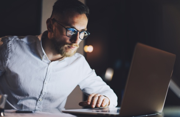 Man in front of computer screen wearing glasses