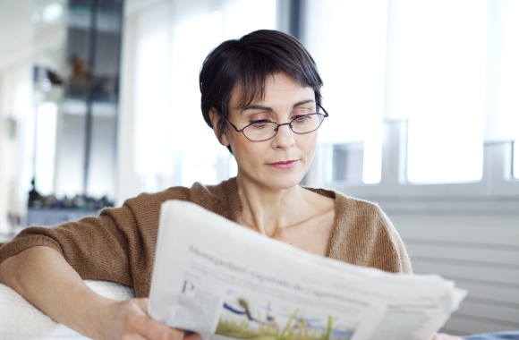 Woman reading newspaper with glasses
